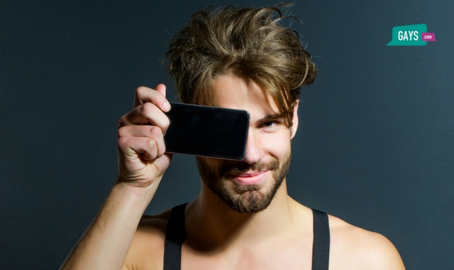 Handsome Man Holding Up A Mobile and Smiling