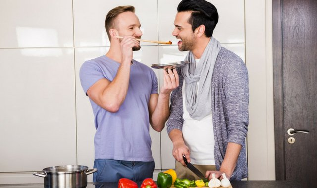 gay couple at home enjoying cooking a meal