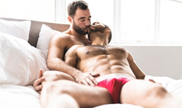 two gay men lying on the bed kissing